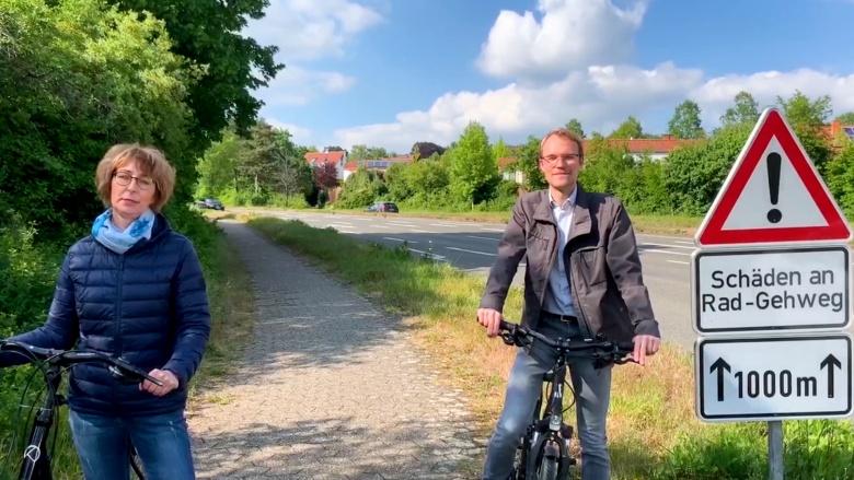 Maria Schlechter-Heims und Dr. Christian Untrieser stehen mit dem Fahrrad an der Bergischen Allee in Erkrath-Hochdahl. Rechts im Bild steht ein Straßen-Warnschild: Schäden an Rad-Gehweg, 1000m.