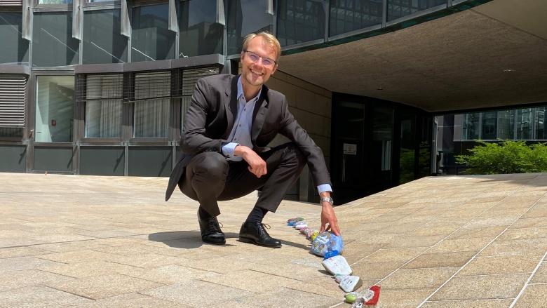 Dr. Christian Untrieser kniet fröhlich vor dem Landtag Düsseldorf neben einer Reihe bunt bemalter Steine.