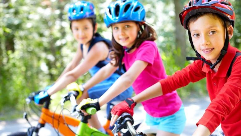 drei Kinder in bunter Kleidung und mit Schutzhelm auf Fahrrädern