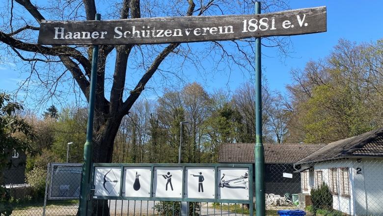 """Holzschild über dem Eingangstor mit der Aufschrift """"Haaner Schützenverein 1881 e.V."""". Auf dem Tor sind fünf Piktogramm-Tafeln angebracht. Sie zeigen die Aktivitäten im Schützenverein."""
