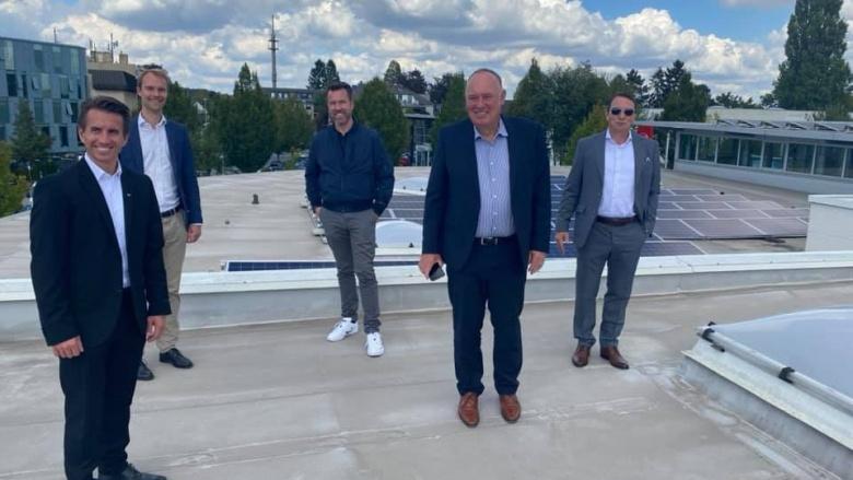 Dr. Christian Untrieser und andere auf dem Dach von BMW Hans Brandenburg GmbH. Das Dach ist mit Photovoltaikanlagen ausgestattet.
