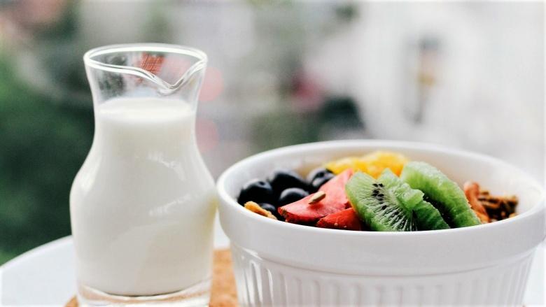 Glaskännchen gefüllt mit Milch daneben eine weiße Keramikschale mit Obst (Kiwi, Blaubeeren, Erdbeere u.a.)
