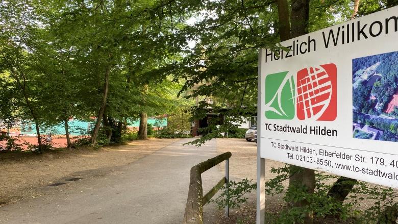 """Draußen am Eingangsbereich des TV Stadtwald Hilden mit einer """"Herzlich Willkommen""""-Tafel."""