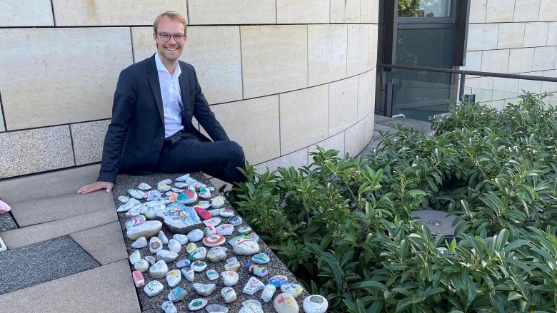 Dr. Christian Untrieser sitzt vor dem Landtag mit den bemalten Wunschsteinen der Städtischen Gesamtschule Haan.