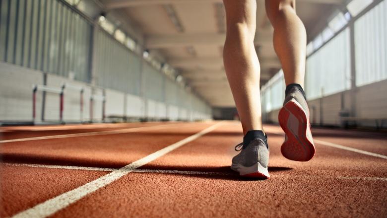 Beine eines Läufers von hinten auf einer Tartan-Rennbahn