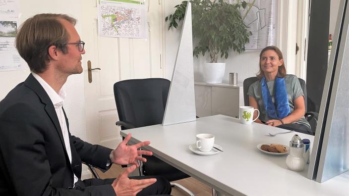 Dr. Bettina Warnecke und Dr. Christian Untrieser reden miteinander. Sie sitzen sich an einem Schreibtisch gegenüber.
