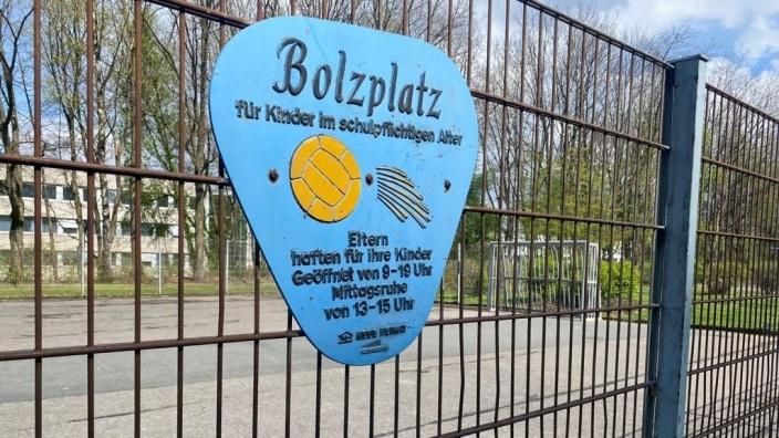 """Ein blaues Schild mit der Aufschrift """"Bolzplatz"""" an einem Gitterzaun. Im Hintergrund ein heruntergekommener, betonierter Bolzplatz mit einem Fußballtor aus Metall."""