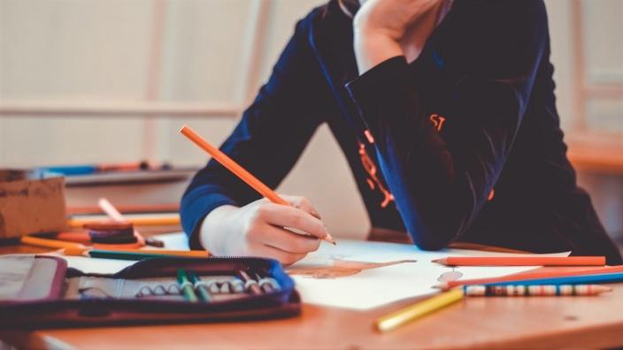 Ein Kind hält einen Buntstift in der Hand und denkt nach. Es hat das Kinn in die andere Hand gestützt. Auf dem Tisch liegen Papier und Stifte.