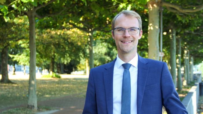 Dr. Christian Untrieser im Park mit grünen Laubbäumen